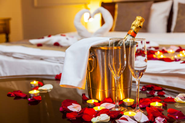 Hotel room for a honeymoon Hotel room for a honeymoon: a table with a fruit plate and candles, in the background a bed decorated with swans of towels and rose petals luxury hotel room stock pictures, royalty-free photos & images
