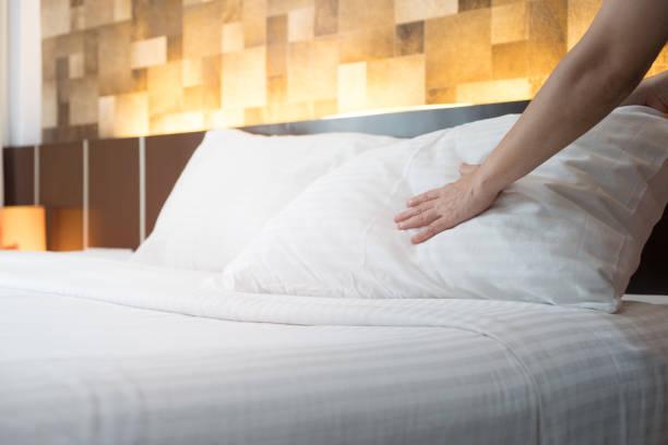 hotel zimmerservice händen eingerichtet von weißen kissen auf dem bett im hotel - verwandlungskissen stock-fotos und bilder