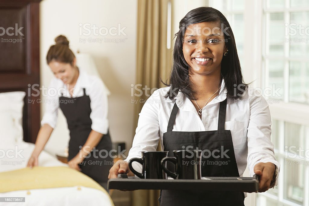 Hotel room service lady offering coffee on tray royalty-free stock photo