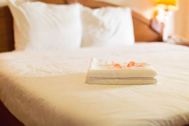 Hotel Room with a stack of towels with rose petals Clean room with towels inn stock pictures, royalty-free photos & images