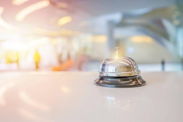 Campana de servicio del hotel en una mesa de cristal blanco. - foto de stock