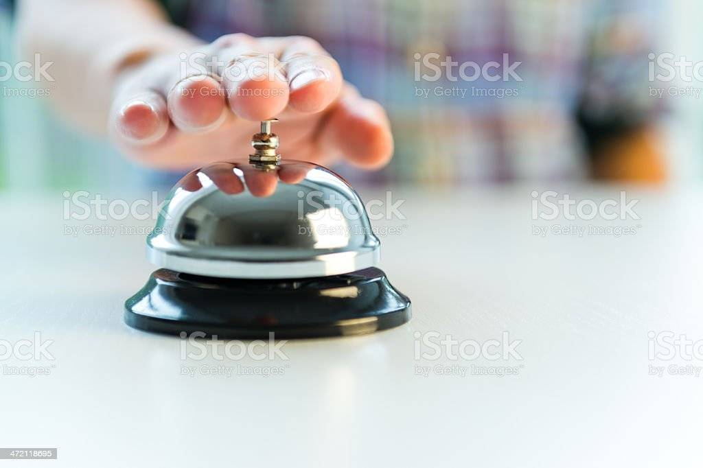 Hotel service bell with customers hand stock photo