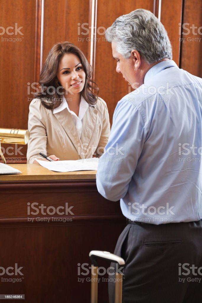 Hotel staff helping businessman check out royalty-free stock photo
