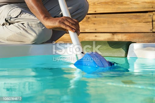 istock Hotel staff worker cleaning the pool 1050284612