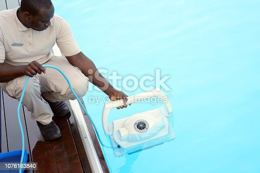 istock Hotel staff worker cleaning the pool 1076163840