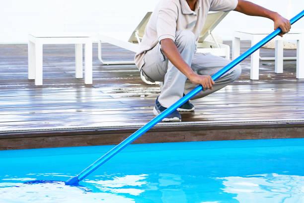Mitarbeiter reinigen den Pool – Foto