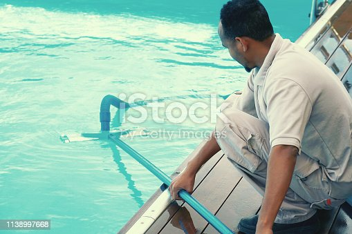 istock Hotel staff worker cleaning the pool 1138997668