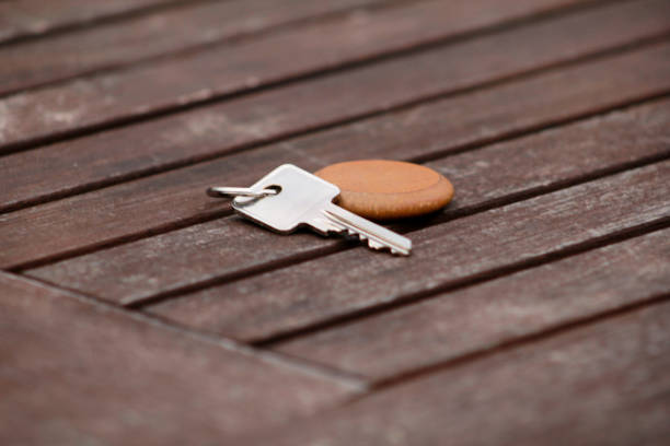Hotel suite key with wooden fob for room on wood table. Room key on wood texture and background. Silver key with a blank label on an old wooden plank. Security and key in hand. Key of my success. stock photo