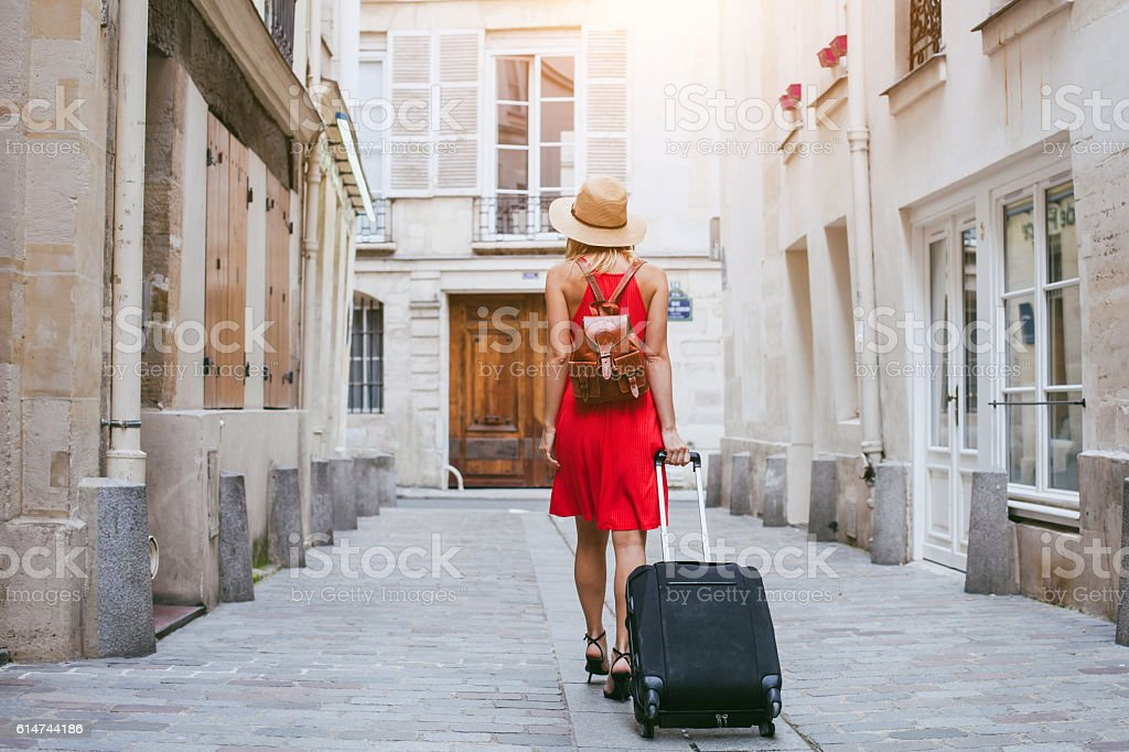 hotel, tourist walking with suitcase on the street