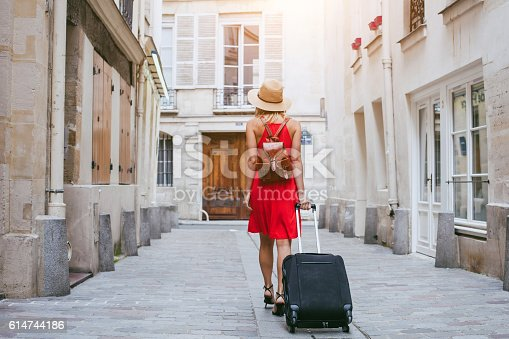 istock hotel, tourist walking with suitcase on the street 614744186
