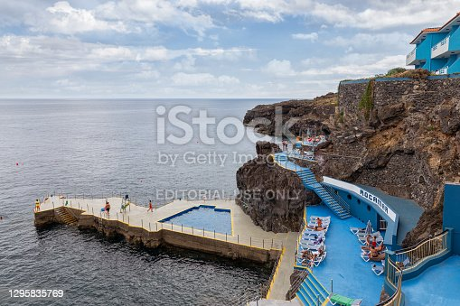 Madeira Island, Portugal - August 02, 2014: Hotel with people in swimming pool at rocky coast near Canico at Madeira Island