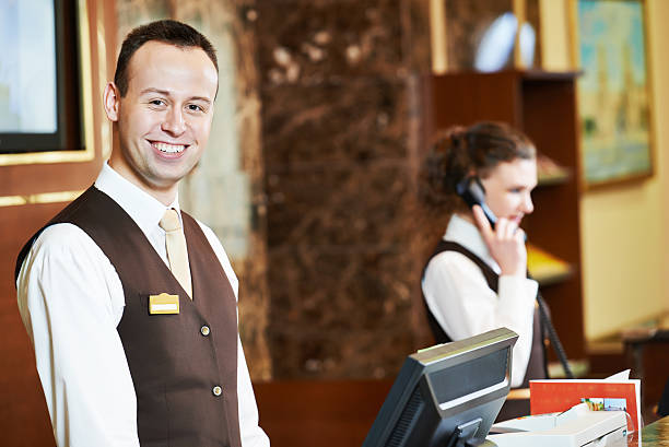 Hotel worker on reception Happy receptionist worker standing at hotel counter concierge stock pictures, royalty-free photos & images