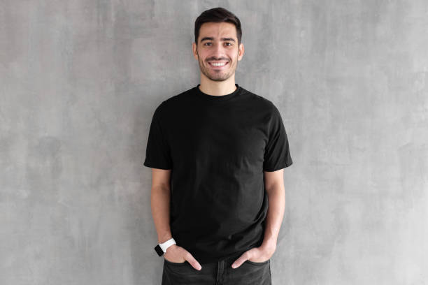 Hotizontal portrait of young man wearing blank black t-shirt and jeans, posing against gray textured wall Hotizontal portrait of young man wearing blank black t-shirt and jeans, posing against gray textured wall black shirt stock pictures, royalty-free photos & images