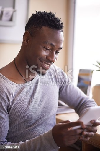 Cropped shot of a handsome young man using his tablet while sitting in a cafe