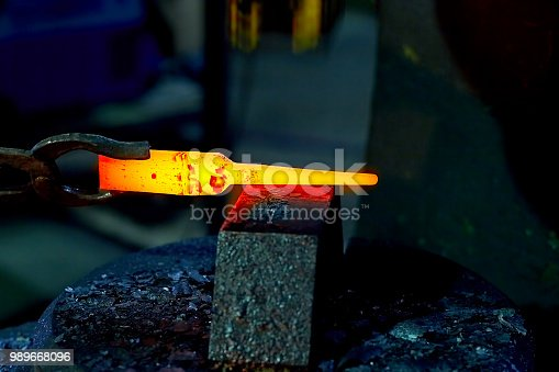 istock hotsteel on the anvil to hold the anvil blacksmith tongs 989668096