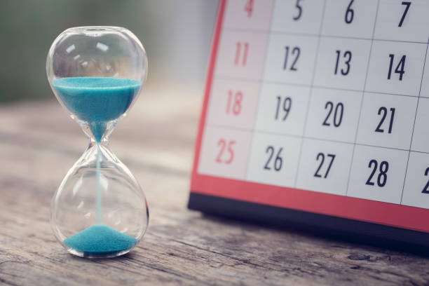 Hour glass and calendar important appointment date, schedule and deadline stock photo