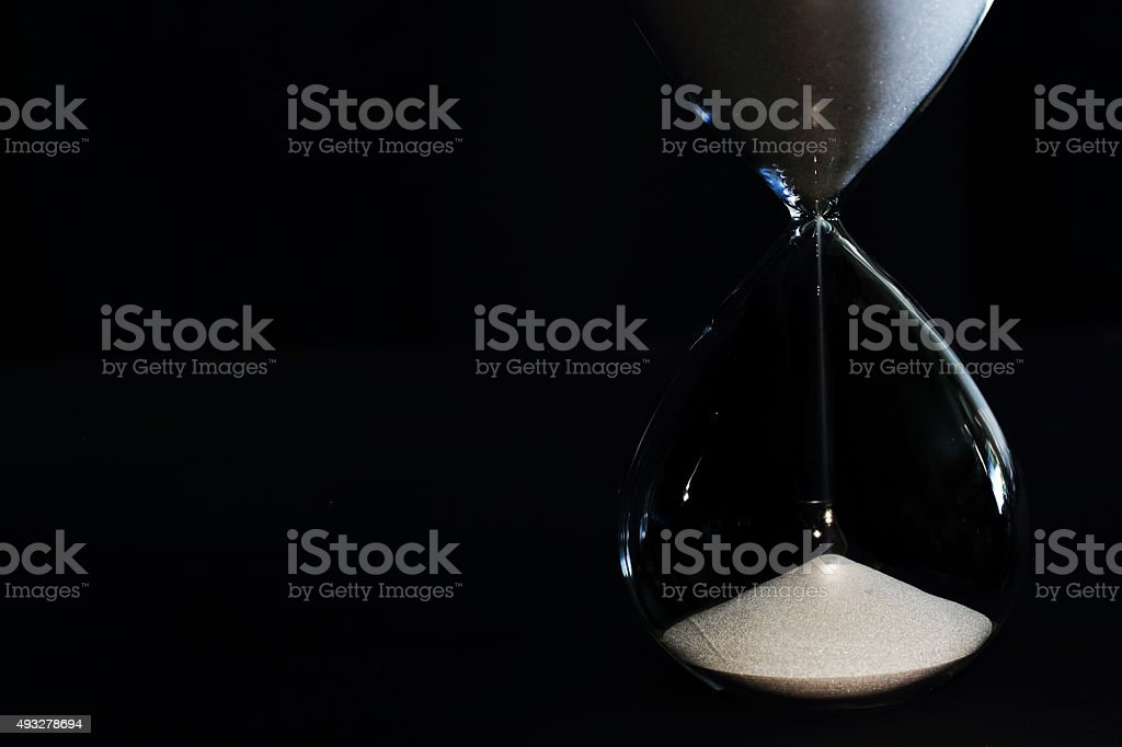Hour Glass on the black background stock photo