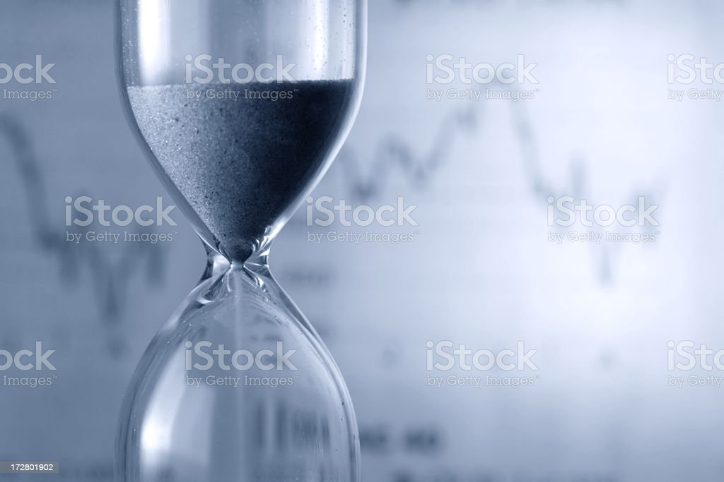 Hourglass against a backdrop of a line graph royalty-free stock photo