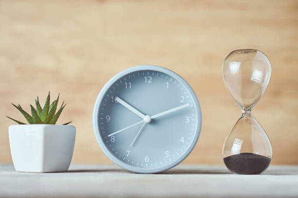 Hourglass, alarm clock and plant on the table, close up Hourglass, alarm clock and plant on table, close up clock hand stock pictures, royalty-free photos & images