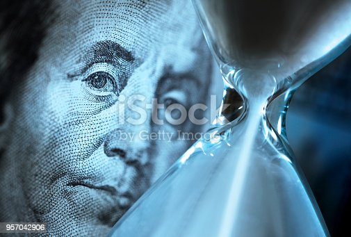 Sand pours through an hourglass as it sits in front of the portrait of Benjamin Franklin on the U.S. one hundred dollar bill.