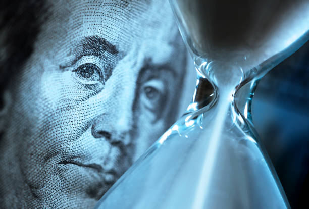 Hourglass And Benjamin Franklin Portrait On One Hundred Dollar Bill Sand pours through an hourglass as it sits in front of the portrait of Benjamin Franklin on the U.S. one hundred dollar bill. time is money stock pictures, royalty-free photos & images