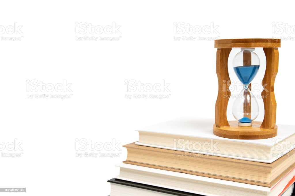 Hourglass and books isolated on white background. stock photo