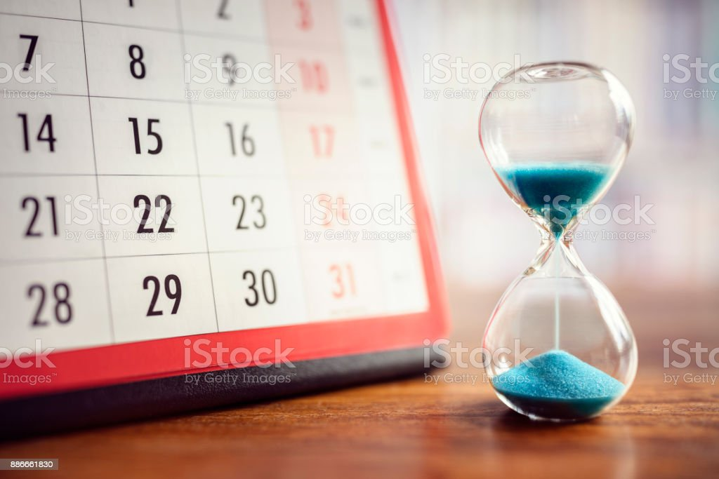 Hourglass and calendar stock photo
