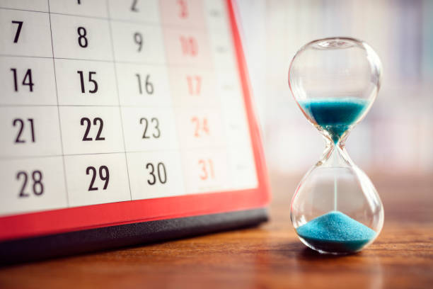 Hourglass and calendar Hour glass and calendar concept for time slipping away for important appointment date, schedule and deadline timer stock pictures, royalty-free photos & images