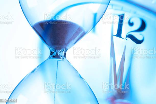 Hourglass and clock about to strike twelve oclock picture id860243132?b=1&k=6&m=860243132&s=612x612&h=f iczboav1b7npimbre iv29lsfwu1dwdyp5hx3 blc=
