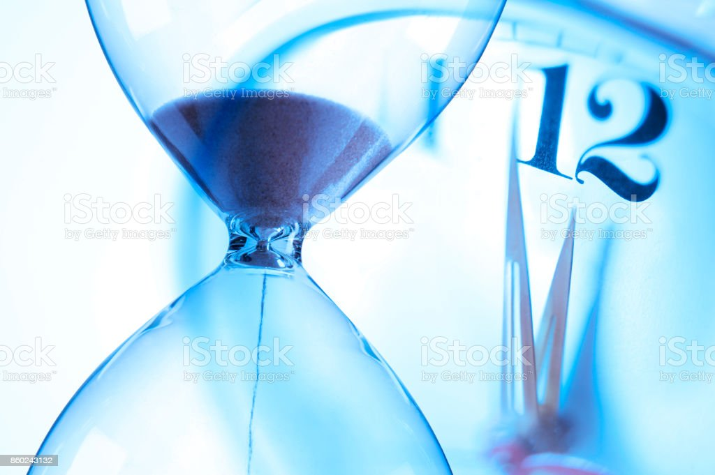 Hourglass And Clock About To Strike Twelve O'Clock stock photo
