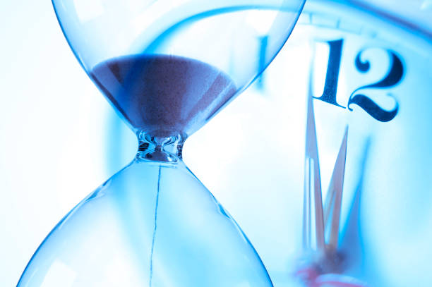 hourglass and clock about to strike twelve o'clock - deadline stock pictures, royalty-free photos & images