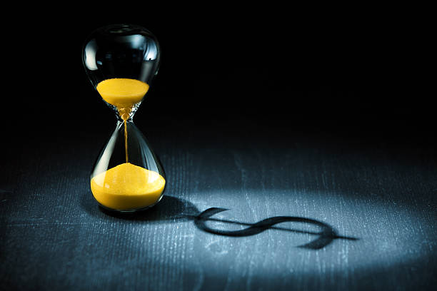 hourglass and dollar shadow - money black background stock photos and pictures