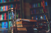 istock Hourglass and Old quill pen, hourglass, books and vintage inkwell on wooden desk in the old office against the background of the bookcase. Conceptual background on history, education, literature topics. 1273452353