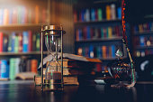 istock Hourglass and Old quill pen, hourglass, books and vintage inkwell on wooden desk in the old office against the background of the bookcase. Conceptual background on history, education, literature topics. 1273452367
