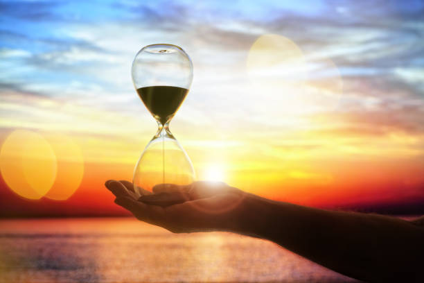Hourglass at sunset concept for time passing stock photo