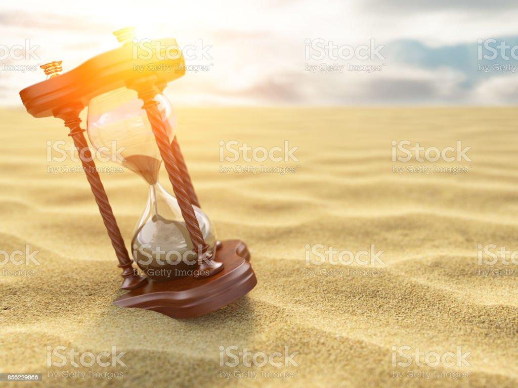 Hourglass clock on sand of desert background. stock photo