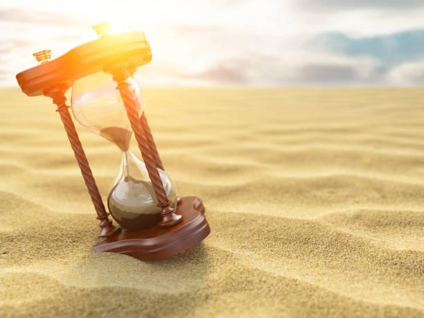 sanduhr uhr auf sand der wüste hintergrund. - sanduhr stock-fotos und bilder