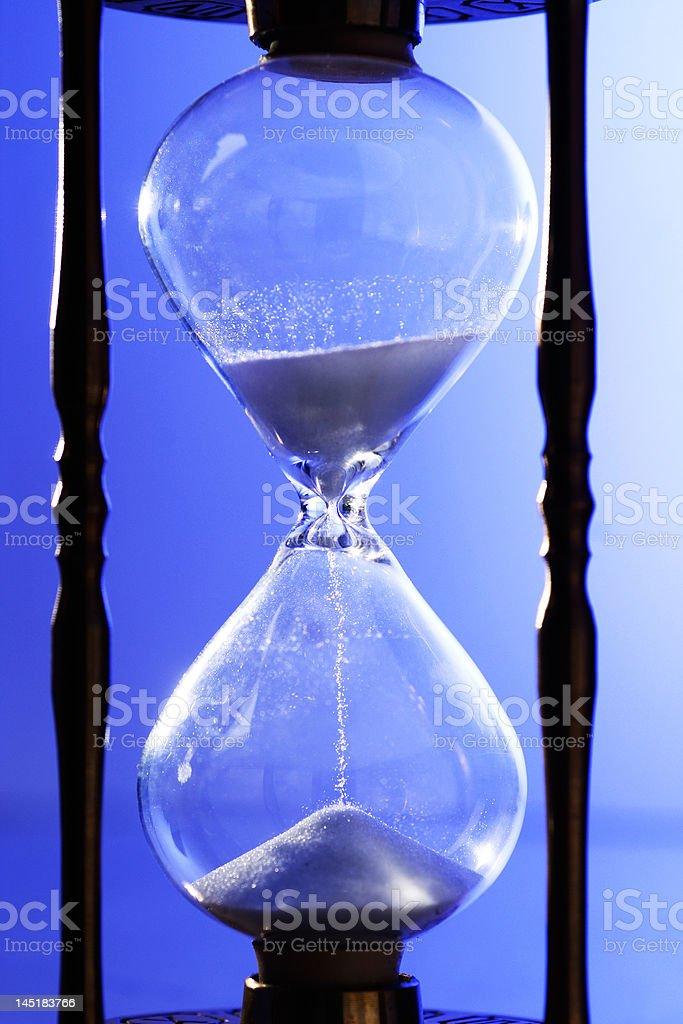 Hourglass closeup on blue stock photo