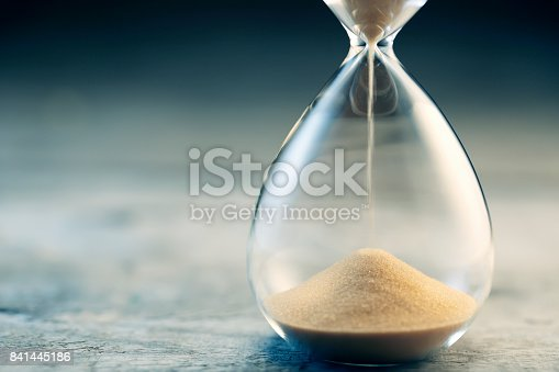 Flowing hourglass on wooden table; Twilight blue