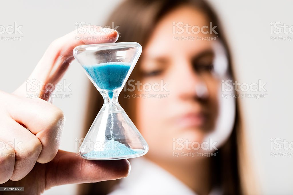 hourglass held by a concerned woman stock photo