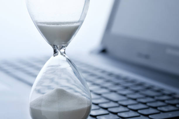 Hourglass in the foreground and laptop keyboard, concept of time spent online. stock photo