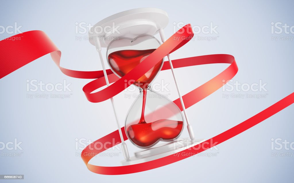 Hourglass in the form of hearts. Entwine red ribbon. stock photo