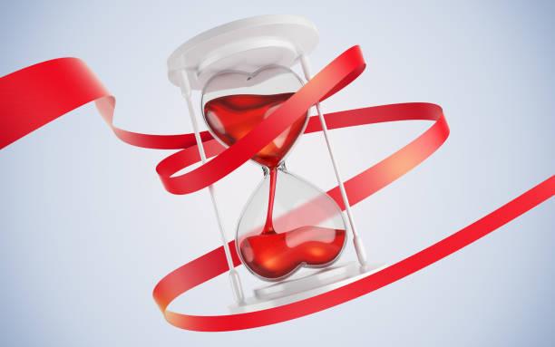 zandloper in de vorm van harten. entwine rood lint. - zandloper icoon stockfoto's en -beelden