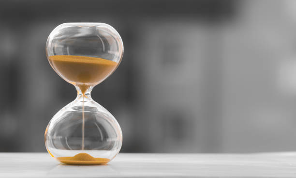 Hourglass on a black white blurred background. Time is money. Hourglass on a black white blurred background. Time is money. deadline stock pictures, royalty-free photos & images