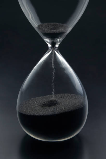 Hourglass on a dark background. Time is money. Business solutions in time. stock photo