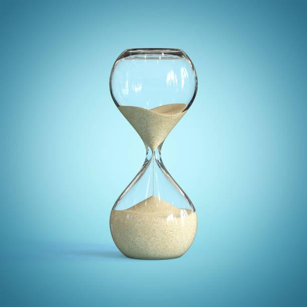 Hourglass on blue background, sandglass stock photo