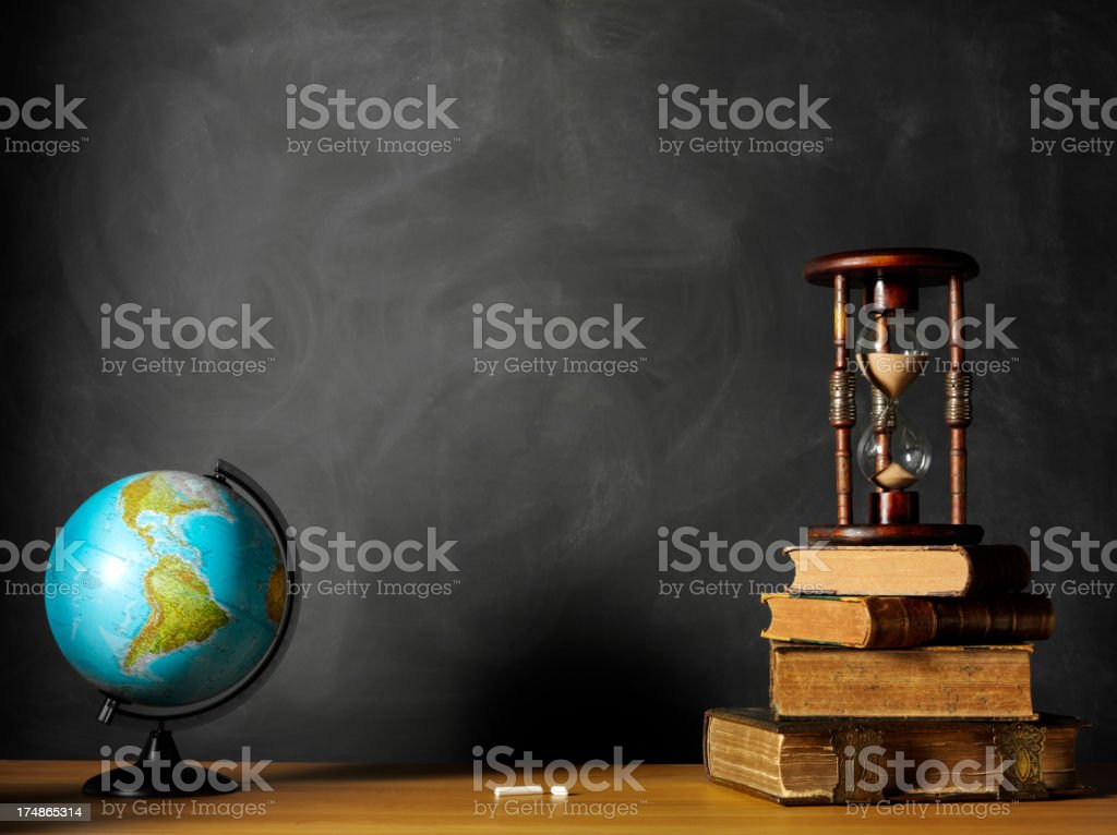 Hourglass on Books with a Desktop Globe royalty-free stock photo