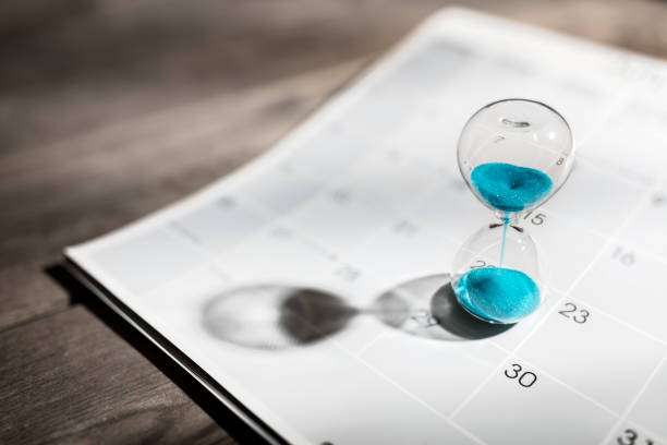 Hourglass on calendar appointment date, schedule and deadline stock photo