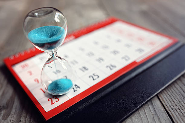 Hourglass on calendar Hour glass on calendar concept for time slipping away for important appointment date, schedule and deadline timer stock pictures, royalty-free photos & images