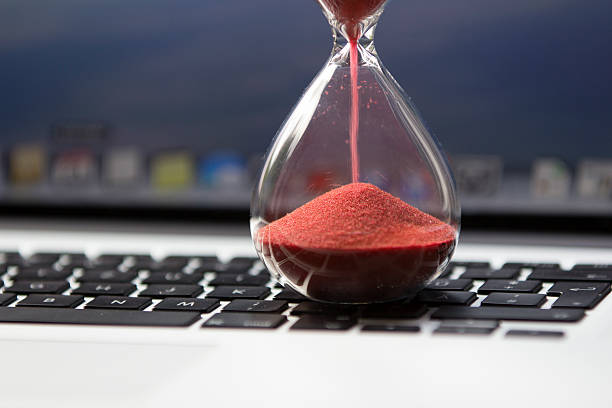 Hourglass on computer keyboard hourglass on keyboard - waiting... slow motion stock pictures, royalty-free photos & images